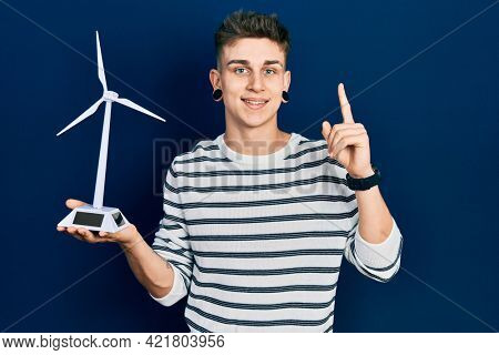 Young caucasian boy with ears dilation holding solar windmill for renewable electricity smiling with an idea or question pointing finger with happy face, number one