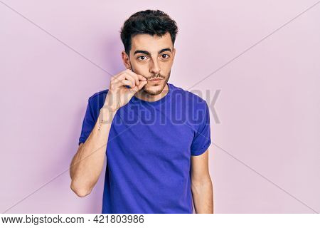 Young hispanic man wearing casual t shirt mouth and lips shut as zip with fingers. secret and silent, taboo talking