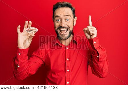 Middle age man holding brilliant diamond stone smiling with an idea or question pointing finger with happy face, number one
