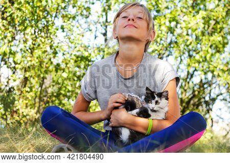 Defocus Blonde Little Girl Caress Cat, Black And White Small Kitten. Nature Green Summer Background.