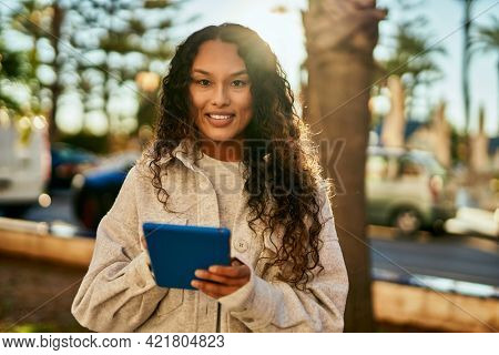 Young latin woman smiling happy using touchpad at the city.