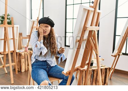 Young hispanic artist woman painting on canvas at art studio yawning tired covering half face, eye and mouth with hand. face hurts in pain.