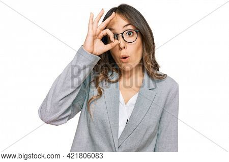 Young brunette woman wearing business clothes doing ok gesture shocked with surprised face, eye looking through fingers. unbelieving expression.
