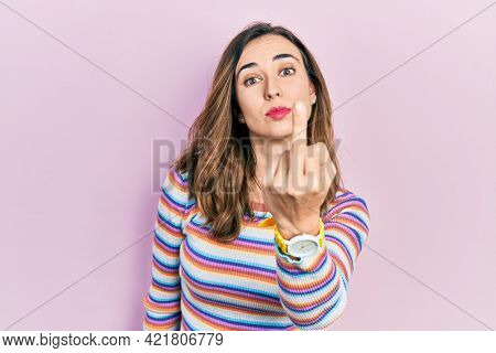Young hispanic girl wearing casual clothes showing middle finger, impolite and rude fuck off expression