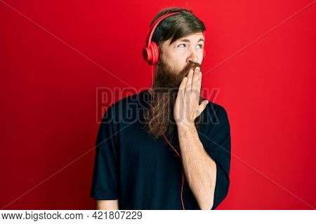 Redhead man with long beard listening to music using headphones bored yawning tired covering mouth with hand. restless and sleepiness.