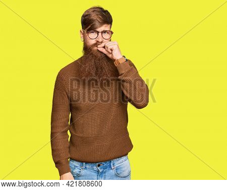 Young irish redhead man wearing casual clothes and glasses mouth and lips shut as zip with fingers. secret and silent, taboo talking