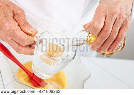 Senior Woman Mixing Water And Vinegar To Prepare Dough For A Traditional Dish From El Valle Del Cauc