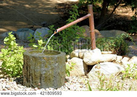 Water Fountain Art Sculpture With Running Water On An Outdoor Patio At A Manicured Garden In A Resid