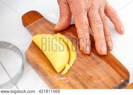 Senior Woman Closing And Cuting An Empanada A Traditional Dish From El Valle Del Cauca In Colombia