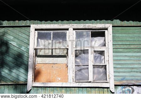 A Dilapidated Wooden Abandoned House. Old Building. Uninhabited House. A Boarded-up Window. No One.