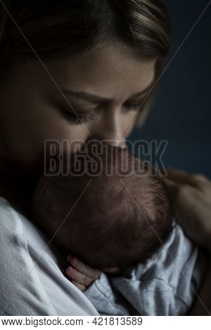 A Young Mother Holds A Newborn Baby In Her Arms. Love And Tenderness. Close-up. Low Key. Vertical.