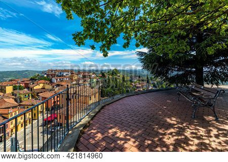 Bench under trees on a viewpoint overlooking small town of Diano d'Alba under beautiful sky in Piedmont, Northern Italy.