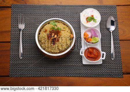 Veg Biriyani , Garnished With Fried Onion ,coriander Leaf And Fried Cashew Nut In An Antique Brass V