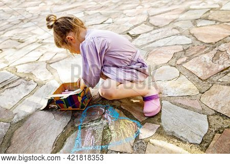 Happy Little Toddler Girl Drawing With Colorful Chalks On Ground Or Asphalt In Summer. Excited Child