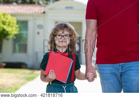 Portrait Of Happy Nerd Pupil Holding Teachers Hand. Father And Son Walking Trough School Park, Holdi