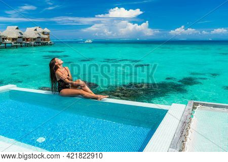 Luxury resort vacation travel woman sunbathing by overwater bungalow swimming pool in Bora Bora, French Polynesia. Elegant happy Asian beauty swimsuit model smooth skin legs at wellness spa hotel.