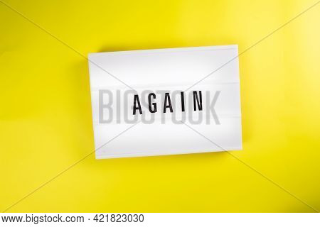 Lightbox With Text Message Again Isolated On Yellow Background. Concept Of Repeat, Return, Iteration