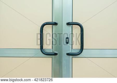 Aluminum Front Door With Arc-shaped Handles. Beige Opaque Door With Black Handles. Emergency Exit. S