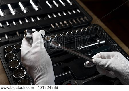 Repairman Hands Closeup In White Gloves Holding Metal Handle Extension Tool Over Dark Background Wit