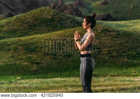 An Attractive And Healthy Young Woman Does Yoga In The Mountains At Sunset. Yoga In The Fresh Air. H
