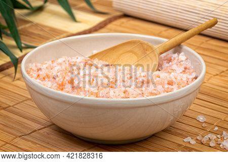 Bowl of coarse red Himalayan salt on bamboo mats