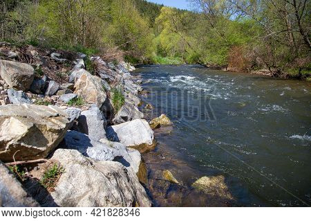 Running Water In Regulated River Surrounded By Green Vegetation In Summer