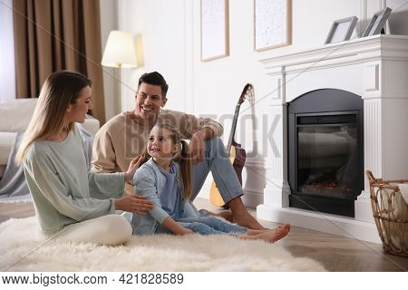 Happy Family Resting Near Fireplace At Home