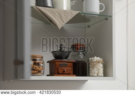 Vintage Coffee Grinder, Sugar And Cookies On Shelving Unit In Kitchen
