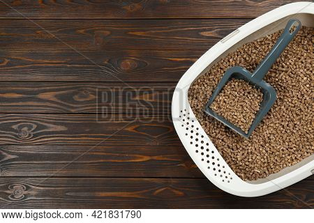 Cat Litter Tray With Filler And Scoop On Wooden Background, Top View. Space For Text