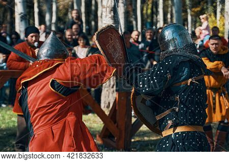 Reconstruction Of Medieval Tournaments Of Knights. A Sword Fight In Front Of A Crowd Of Spectators.