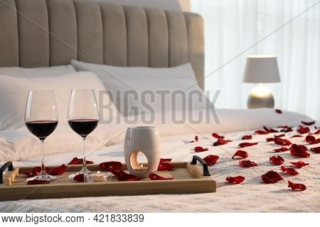 Tray With Glasses Of Red Wine, Candles And Rose Petals On Bed In Room