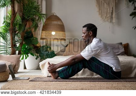 African Young Man Sitting In Paschimottanasana Or Intense Dorsal Stretch Pose, Seated Forward Bend P