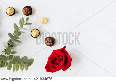 Round nutty chocolates by a red rose