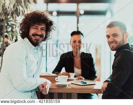 A group of business people on a coffee break use laptops, tablets and smartphones while discussing new business projects.