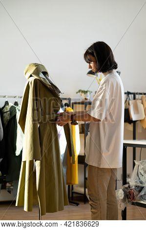 Designer Adjusting Cloak On Mannequin In Studio. Modern Fashion Atelier Worker Work With Model Of Ra