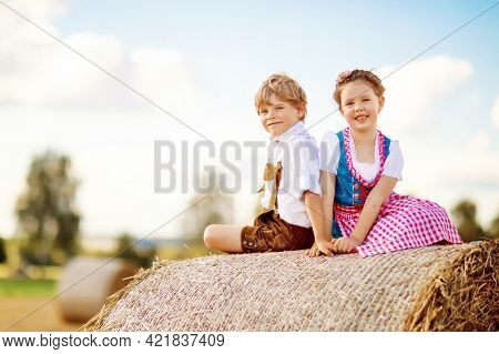 Two Kids, Boy And Girl In Traditional Bavarian Costumes In Wheat Field