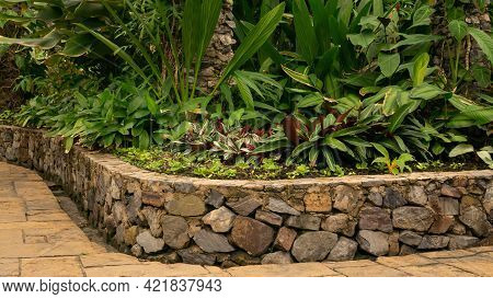 Indoor Garden Decorated With Sandstone Pavement And Stone Brick Wall Flowerbase Container, Greenery