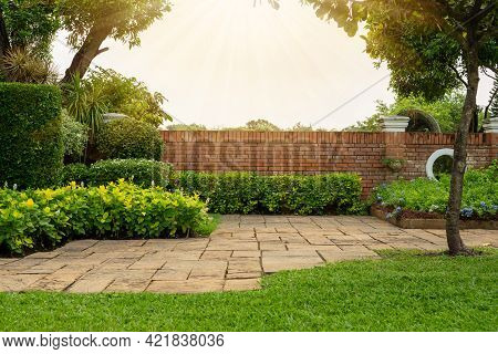 Back And Front Yard Cottage Garden, Flowering Plant And Green Grass Lawn, Brown Pavement And Orange