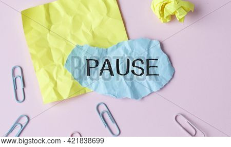 On A Pink Table There Is An Office Sheet Of Paper With The Text Pause. Business Workspace With Calcu