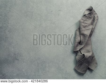 Folded Linen Napkin Or Towel With Copy Space For Design. Gray Linen Towel On Gray Stone Background.