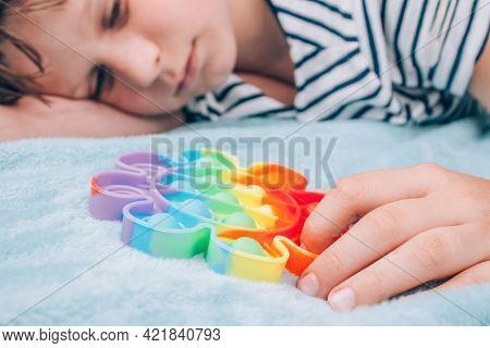 Bored Boy Playing With Rainbow Pop It Fidget Toy. Push Bubble Fidget Sensory Toy - Washable And Reus