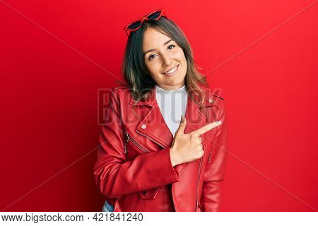 Young brunette woman wearing red leather jacket cheerful with a smile of face pointing with hand and finger up to the side with happy and natural expression on face