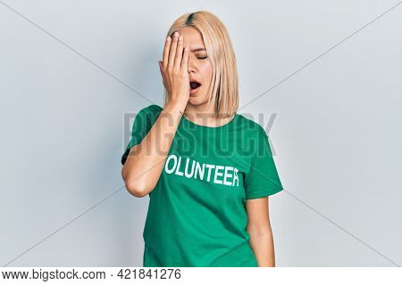 Beautiful blonde woman wearing volunteer t shirt yawning tired covering half face, eye and mouth with hand. face hurts in pain.