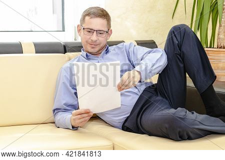 A Young Male Manager With Glasses In A Blue Shirt Lies On The Couch In His Modern Office. Reads A Do