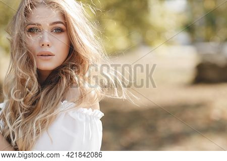 Young Beautiful Blonde Caucasian Woman Is Walking In A Summer Park. Beautiful Girl, Spring Portrait.