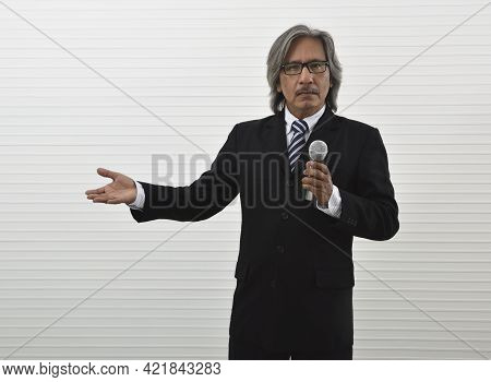 Confident Elderly Asian Businessman In Black Suit Speaking With Microphone And Shows Outstretched Ha