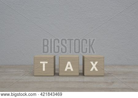 Tax Letter On Wood Block Cubes On Wooden Table Over White Wall Background, Business And Finance Conc