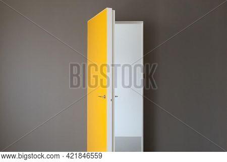 Indoor Interior Open Door, Entrance And Doorways. Bright Yellow Door And Grey Wall