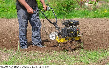 Farmer Man Plows The Land With A Cultivator. Soil Preparation For Sowing. Agricultural Machinery For