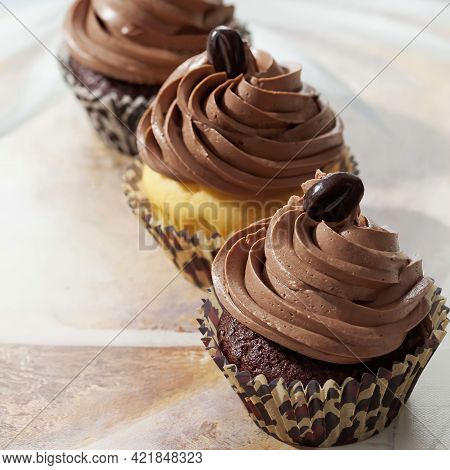 Three With Mocha Beans Decorated Cup Cakes In Paper Cups